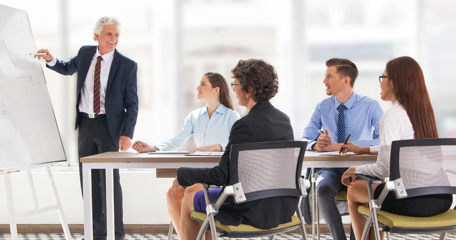 Homem fazendo uma apresentação para um grupo de pessoas sentadas em uma reunião